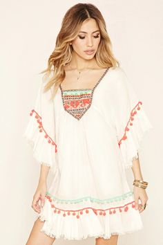 A semi-sheer woven peasant dress by Z & L Europe™ featuring tribal-inspired embroidery, a square neckline, pom-pom trim, a frayed edges, and 3/4 sleeves. #f21brandedshop
