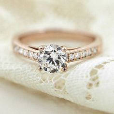 This accented rose gold engagement ring from MiaDonna is set with a 1 carat round cut center stone. Beautifully bridal