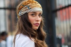 Scarf worn across forehead, atop head, tied in back. Below, spilling out of scarf, long, brown waves. | TheyAllHateUs