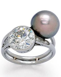 An Antique Natural Pearl and Diamond Ring, circa 1910. The Toi et Moi design set with a dark grey natural button pearl measuring approximately 10.0 mm, and a collet-set old European-cut diamond weighing approximately 2.45 carats, accented by small old mine-cut diamonds, to a twinned shank, mounted in platinum. #antique #BelleEpoque #Edwardian #ring