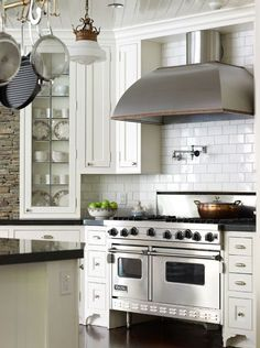white subway tile, glass cabinets, classic kitchen design beadboard ceiling, off-white kitchen cabinets with Absolute Black Granite, copper pot rack, off-white kitchen island, pot filler and brick wall.