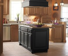 Timeless light oak cabinets pair with a beautiful black kitchen island and range hood for a look that is striking yet surprisingly welcoming to all. Adding decorative feet creates a furniture feel, while the raised peninsula keeps visitors close at hand, yet ensuring that they don't get underfoot.