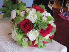 Wedding bouquet of white roses, bells of Ireland, green cymbidium orchids and hot pink roses.