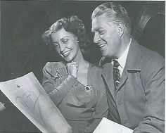 This is my new acquisition and my new favorite photo of them (also using this as my profile photo). Never seen this particular pose before. This is an original, vintage photo of Jeanette and Nelson during one of their radio appearances together...he has her tucked close against his shoulder, both of them happily looking at a drawing of a heart with their initials with Cupid's arrow through it. - ESCANO COLLECTION