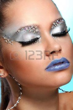 Retrato de mujer con maquillaje artístico y pedrería sobre fondo Foto de archivo