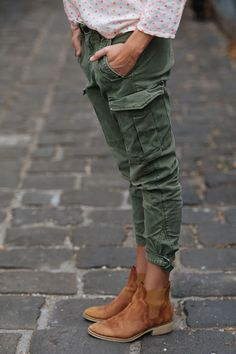 Green pants, camel boots and polka dots shirt. Amazing. Latest trends.