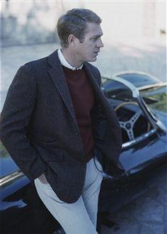 American actor Steve McQueen (1930 - 1980) leaning on his Jaguar D-Type XKSS sports car, 1965.