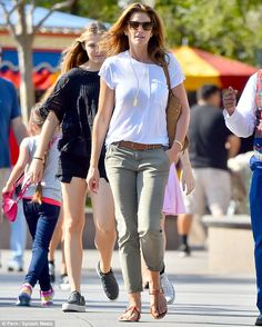 Casual chic: Cindy dressed down in a loose white blouse and faded green trousers...