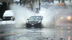 As snow changes to rain and temperatures warm, street flooding is occurring including at the base of the Fore River Bridge, on Bridge St., in Weymouth, where a car trudges through, Tuesday, March 14, 2017.  Gary Higgins/The Patriot Ledger
