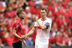 (LtoR) Albania's midfielder Ermir Lenjani shakes hands with Switzerland's defender Stephan Lichtsteiner after a clash during the Euro 2016 group A football match between Albania and Switzerland at the Bollaert-Delelis Stadium in Lens on June 11, 2016. / AFP / MARTIN BUREAU