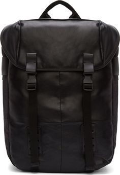 """Unstructured leather and textile backpack in black. Grosgrain carry handle at top. Foldover flap closure with two pinch-buckle fastenings at face. Bungee drawstring closure at throat. Patch pockets at exterior face. Adjustable shoulder straps at back. Neoprene device pouches at interior. Logo stamped textile lining. Tonal stitching. <Br><Br> Measures approx. 11"""" length x 18"""" height x 6"""" width."""