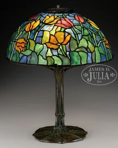 """TIFFANY STUDIOS TULIP TABLE LAMP. Tiffany Studios table lamp has leaded glass shade with red, yellow and orange tulips with nicely mottled green leaves and stems. All set against a blue confetti glass background. Signed on the inside edge with small tag """"Tiffany Studios New York"""". Shade rests on a Tiffany Studios Model #461 bronze art nouveau base, known as penguin design, with organic form foot and stem leading to a four arm spider and single socket. The base is finished in a rich brown…"""