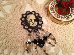 This Handmade Lady Skull Brooch/Pin is made of high end beads and stones,     consisting of:     Handmade Black and Antique Look Ivory Cabachon Lady Skull Cameo Pendant,     Large and Small Swarovski Crystal Accent Beads,    Black Onyx Cross Beads,     Hematite Accents,     Freshwater Pearls,    Black Onyx Faceted Bead,    Large Vintage Look Frame.     This is a substancial brooch or pendant, at least 4 inches in length...$25.