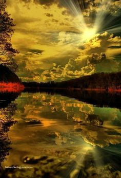 Reflection of Clouds in lake. Sun breaking through clouds.