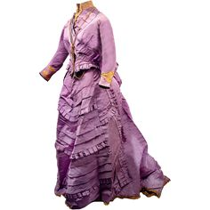 This is a stunning and elaborate two-piece lilac silk faille bustle gown with full waterfall train. The bodice is fully lined and boned and closes 1870's
