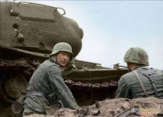 Eastern front 1943 German soldiers take cover against a destroyed Soviet KV-1 tank in Lake Ladoga, Leningrad, September 15, 1943.