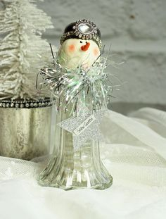 2016 edition handmade snowman  This cute little snowperson would make the perfect gift for your favorite snowman collector! She is just filled with wintery Christmas cheer. Hey, if shes a gift to yourself all the better! Her head is hand sculpted and hand painted by me :). She has a little carrot nose and beady little eyes with a twinkle in then. Rosy pink cheeks finish out her face. Her little hat is a silver plate shaker top adorned with a sparkly vintage style cabochon and is edged in…