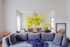 Sala de estar tem sofá cinza e ao fundo sala de jantar com obra de arte.