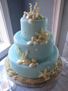Almond cake with white chocolate cream cheese icing covered in satin ice baby blue fondant.  White chocolate shells and coral.