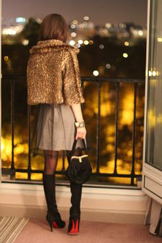 Leopard print coat, taupe skirt and Louboutin boots on balcony.