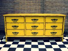 Beautiful large chest of drawers or side board with nine drawers featuring wide tapered legs. Each drawer has the original large and chunky decorative brass handles. Entire piece has been painted in bold deep yellow and finished in a distressed style.  SOLD.