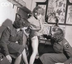 Womens Royal Army Corps member showing new tattoo on her leg to fellow enlistees. WWII, wartime.
