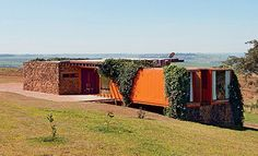 Built by Rafael and Ana Borges and designed by Jorge Siemsen this weeks featured Shipping Container House  is unusual in that it uses Masonry and Insulated Containers in its construction.  At just  130 SQM of living space  this hybrid construction home features  masonry walls in the the kitchen and service areas with re-purposed stones and brick  harvested on the farm from previously demolished construction.