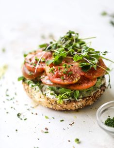 These avocado tomato sandwiches are the perfect lunch! Complete with veggie cream cheese, smoked sea salt, fresh chives and microgreens, the sliced avocado and heirloom tomatoes are sandwiched on an everything bagel for a flavor explosion. I howsweeteats.com #avocado #tomato #sandwich #healthy #lunch