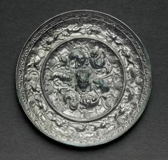 A silvery bronze circular 'Lion and grapevine'mirror, Tang dynasty (AD 618-907)