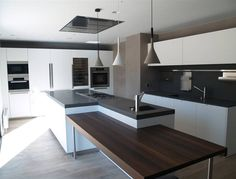 Boffi kitchen with white lacquer, grey countertop, wood seating area and Best fan and Foscarini aplomb lights. Pretty amazing.