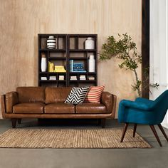 Peacock blue chair works beautifully with the brown leather couch. Don't be afraid to mix and match your colours!