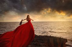 Woman in Red Dress with a Violin by the Sea. Photo by Elena Paraskeva.