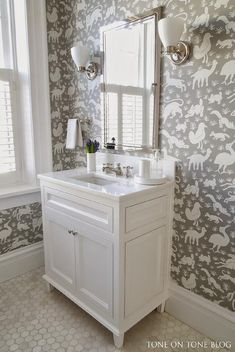 White and gray kid's bathroom features walls clad in white and gray animal print wallpaper, Thibaut Nairobi Wallpaper, lined with a framed inset medicine cabinet illuminated by white glass uplight sconces over a single washstand with feet topped with white marble alongside carrera marble hex tile floor.