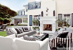 "Martyn Lawrence Bullard covered roll-arm sofas and chairs in Perennials fabrics for a black-and-white outdoor living room in a Los Angeles house: ""I wanted it to look like indoor furniture had been dragged outside."""