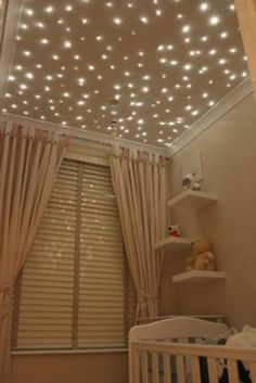 Stars twinkle on the ceiling of this baby nursery putting a twist on the traditional moon and stars nursery theme.