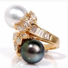 This stunning estate dual pearl diamond ring is crafted in solid 18K yellow gold. This ring is centered with one genuine lustrous white south sea pearl approx 12mm and one lustrous genuine black south sea pearl approx. 12mm. It is accented with some 12 genuine Baguettes diamonds and 8 genuine marquise diamonds all approx. 5.00ct, H color, VS1 clarity channel set. This ring is in excellent condition!! Weight is approx: 18.3 Grams Width/Height is approx: 23mm x 26mm Ring Size is approx…