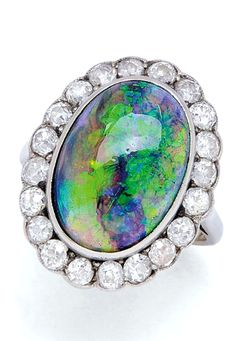 An Antique Crystal Black Opal and Diamond Ring, circa 1920 Centering an oval crystal black opal measuring 15.8 mm by 11.2 mm by 5.33 mm, surrounded by old mine-cut diamonds totalling approximately 1.20 carats, mounted in platinum and 18k white gold