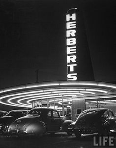DRIVE INN RESTAURANT CALLED HERBERT'S ARCHITECTURALLY DESIGNED BY WAYNE MCALLISTER HIMSELF. COMMERCIAL VERNACULAR BUILDINGS LIKE HERBERT'S RESPONDED TO THE DEMANDS OF THE NEW MACHINE AGE AND THE CAR ATLEAST AS IMAGINATIVELY AS MANY BETTER KNOWN MODERN BUILDINGS. THE CIRCULAR PLAN AND NEON PLYON WERE TAILORED TO THE CAR CUSTOMER.
