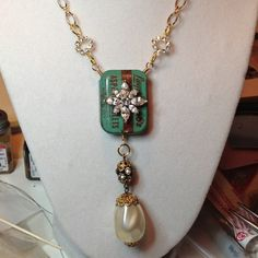 Vintage aspirin tin embellished with vintage costume jewelry made into a necklace. By K. Farley.