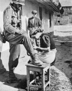 """Polish woman sews pants for a German Sergeant from the """"Edelweiss"""" division, 1939."""