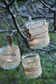 baby food jars wrapped with burlap & strung with wire for hanging as outdoor tea lite holders