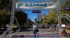 Jim Moody, of Eudora, raises his arms in celebration as he crosses the finish line of the Kansas Half Marathon Sunday afternoon in downtown Lawrence. Despite being the last runner to cross the line, Moody won a $150 dollar gift certificate for Ad Astra Running.