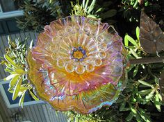 This exquisite vintage glass, and art glass plate flower is simply striking! It is made only of high quality collectable vintage glass. It is approx. 10 inches in width. Each forever flower has been created to be staked outdoors in the garden. Glass flowers may also be enjoyed indoors, sitting on a plate stand, near a sunny window. I have used four pieces of glass in this one of a kind work of garden art! An iridescent finished, multi colored, carnival glass inspired piece creates the shape…