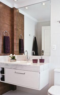 A cerâmica clara em paredes e piso compõe uma base neutra que ressalta a faixa de porcelanato com padrão madeira.