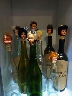 """Botellas personalizadas, Denota: botellas adornadas con cabezas de muñecas. Connota: niños que sufren el del """"FAS""""  síndrome alcohólico fetal."""