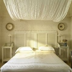 Four whitewashed shutters—topped with a length of decorative, carved molding—make up this beautiful headboard.