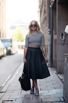 Black midi skater skirt with a crop topA soft flared skirt with a striped top showing off your midriff. An essential for the season! Source: Stockholm street style