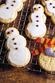 The simplest and sweetest way to decorate these sweet snowmen is with a glaze of powdered sugar icing, miniature chocolate chip eyes, and buttons, and a gumdrop piece for a nose. #christmascookies #decoratedcookies #forkids #cuteholidaycookieideas #easy #bhg