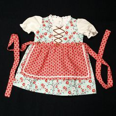 A fanciful combination of pink and red blossoms on a pale aqua background, this charming baby dirndl has brown faux lacing up the front, eyelet lace at the neckline, and is accented with brown buttons. The detachable red and white apron is trimmed with white rickrack and features the traditional long strings that wrap around to fasten in the front. The dress shown is size 0-3 months.
