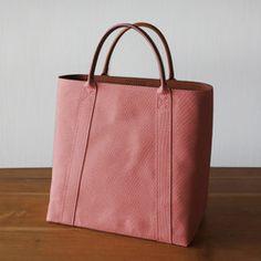 < コンセプト >日本製の帆布とイタリア製バケッタレザーを使用し丁寧な製法で上品な雰囲気に仕上げたシンプルな帆布のトートバッグ< 特 徴 >●小さく見えつつ収納力のある上すぼまりフォルム●クッション素材を内張りすることでハンドバッグのように自立する構造●握り心地の良い革巻きハンドル< こだわり >●ハンドバッグの製法(ヘリ返しなど)を取り入れた上品で丁寧な縫製●革の端面は丁寧なコバ塗り仕上げ●使うほどに味わいの増すイタリア製バケッタレザー使用< 収 納 >●クッション内張りで壊れやすいもの(スマホやカメラなど)を入れても安心●A5ノート/スマートフォン/財布/ミラーレスカメラ等を収納可能●スマートフォンや定期入れを収納できる内ポケット< 寸 法 >本体サイズ:縦25cm 横25cm 奥行き15cm持ち手:26cm< 素 材 >本 体:パラフィン加工10号コットンキャンバス(日本製)(色:生成)裏 地:コットンツイル(日本製)(色:ネイビー)皮 革:タンニン鞣し牛革(イタリア製)(色:ブラウン)< その他…